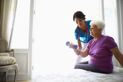 A nurse exercising with an elderly woman