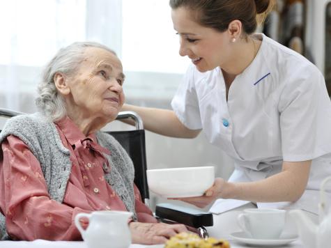 Nurse helping an elderly woman eat.
