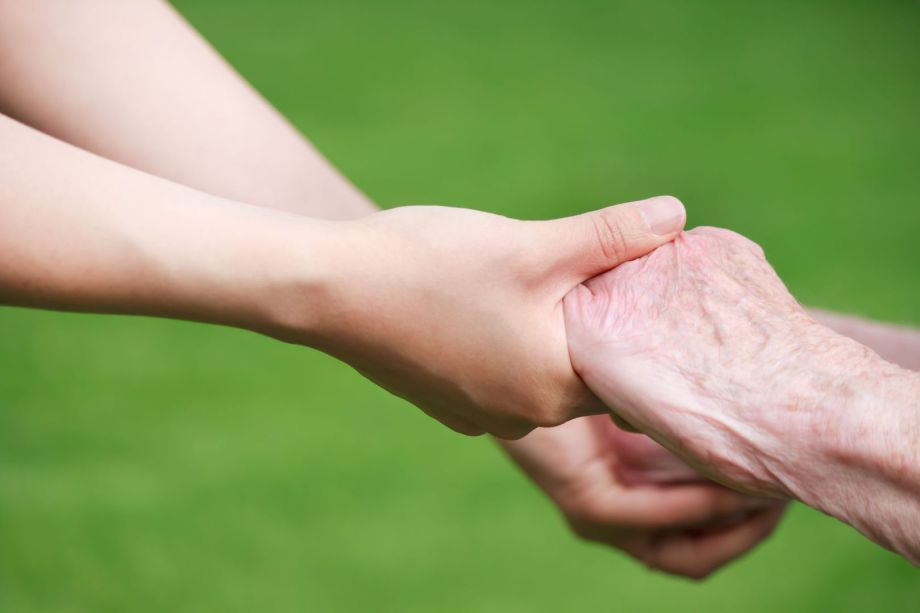 Nurse and elderly man holding hands.